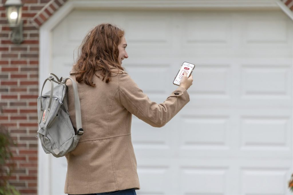 a woman looking at her phone outside the garage | Be Informed Home Inspections | Connectivity Dallas