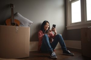 a girl sitting looking at her phone smiling | be Informed Home Inspections | moving made easy dallas fort worth