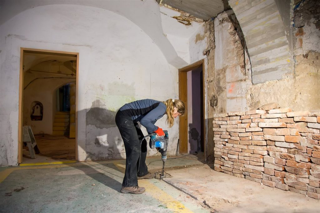 woman drilling the basement floor | Be Informed Home Inspections | Bathroom in the basement Fort Worth